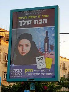 """لافتة في اشوارع مدينة الرملة تظهر امرأة ترتدي الحجاب، مكتوب على البوستر: """"فقط البيت اليهودي قوي من سيحافظ على الرملة يهودية"""""""